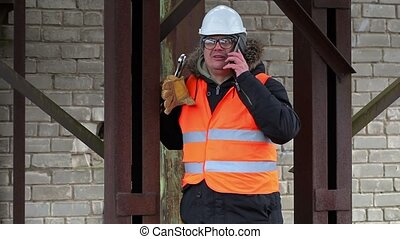 Worker with adjustable wrench and phone