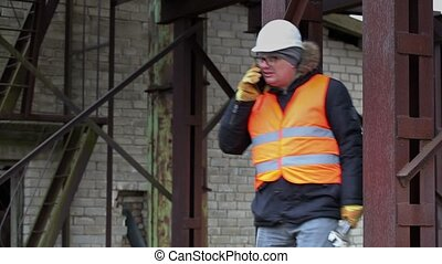 Worker with adjustable wrench talking on cell phone