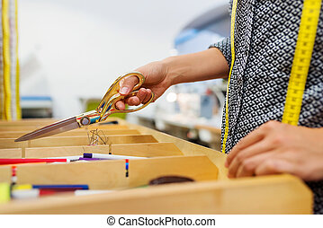 Unrecognizable tailor woman taking scissors out of a drawer...