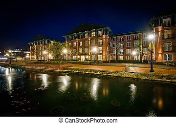 Apartment buildings along Carroll Creek at night, in...