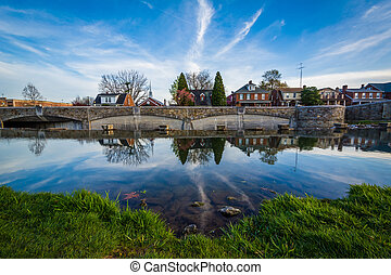 Bridge and houses reflection in Carroll Creek, in Frederick,...