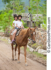 Two asian sisters riding a horse