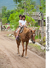 Two asian sisters riding horse