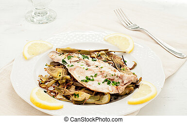 Fish sea bass cooked in a pan with the artichokesartichokes finely chopped and cooked in a pan