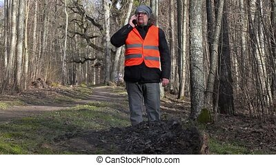 Inspector with smartphone near burning leaves - Inspector...