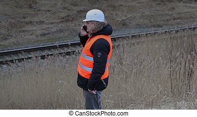 Railroad worker with smart phone near railway