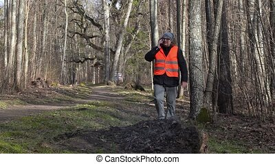 Inspector with smartphone walking to pile of burning leaves...