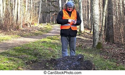 Inspector using tablet PC near to pile of burning leaves -...