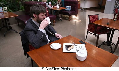 Businessman sitting in a cafe drinking coffee He writes on...