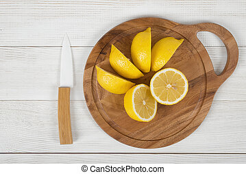 Sliced and whole lemons on cutting board with a knife next...