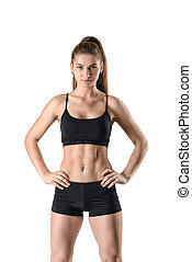 Beautiful sporty woman demonstrating press stomach and looks...