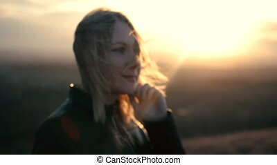 Beautiful girl watching the sunset and smiling, solar flare.