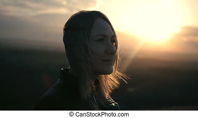 Beautiful girl watching the sunset and smiling, solar flare