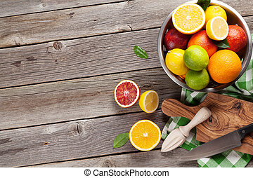 Fresh citrus fruits in colander on wooden table. Top view...