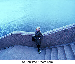 Pensive woman posing on granite river embankment a lot of space for text