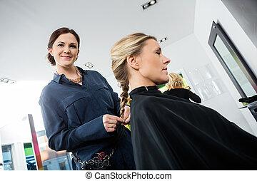 Smiling Female Hairdresser Braiding Clients Hair - Portrait...