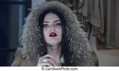 Beautiful brunette in fur coat posing on camera HD