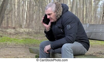 Man using smart phone in the park on bench