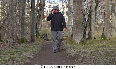 Man using smart phone on path in the park