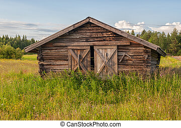 Summer in northern Sweden - Traditional hay barn typical for...