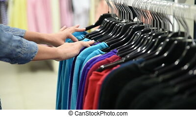 female customer looking for T-shirts in a fashion store -...