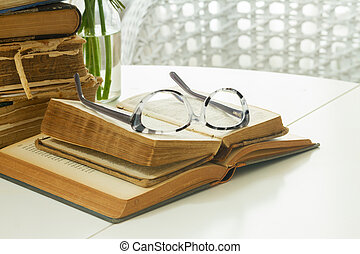 Old books with rose flower - Pile of old books with glasses...