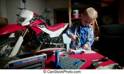 Little Mechanic Fixing Toy Car in Garage - Little boy is...