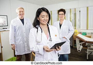 Doctor Holding Digital Tablet While Standing With Colleagues