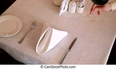 The waiter serves wine and a dish at the restaurant HD