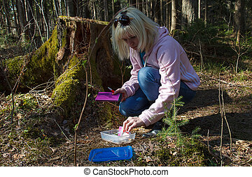 Geocaching in the forest - A woman geocaching in a green...