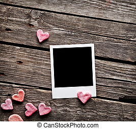 Blank instant photo and sweet red hearts On old wood...