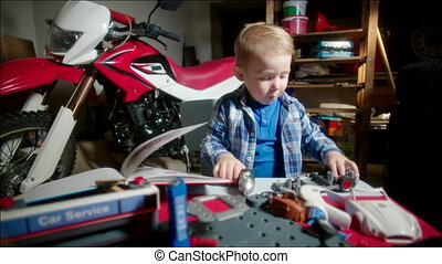 Little Boy Dismantling Toy Car - Little boy is playing the...