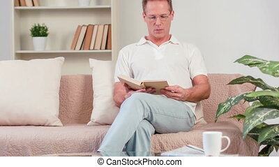Pleasant man sitting on the couch - The last page. Cheerful...