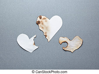 Different paper hearts. Partially damaged. Closeup on gray...