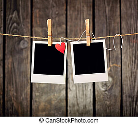 Blank instant photos and small red paper heart hanging on...