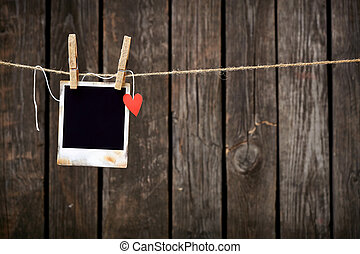 Blank instant photo and small red paper heart hanging on the...