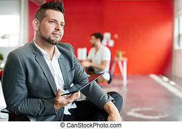 Confident male designer working on a digital tablet in red creative office space