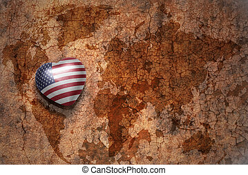 heart with national flag of united states of america on a vintage world map crack paper background. concept