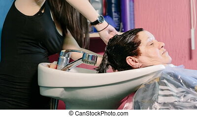 Hairdresser wash head to the client with dyed hair Video...