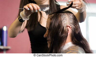 Hairdresser dye the hair of the old woman. Video full hd.