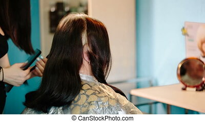 Hairdresser combing the hair to the client.