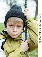 Lonely child in coat holding rope - Close up view on lonely...