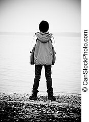 Rear view on boy facing lake - Black and white rear view on...
