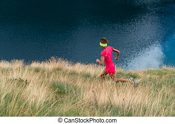 Female athlete trains in a mountain meadow
