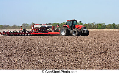 Farm Tractor - Farm tractor working in a field tilling the...