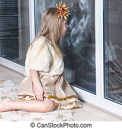 young girl looking out the window