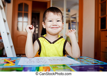 Little boy happy sitting at table after drawing, pre-school home education.