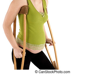 Pregnant Woman with Crutches - Nine month pregnant woman...