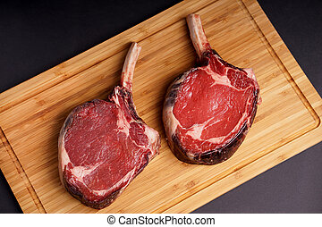 Tomahawk Steak on wood board - Raw Dry aged tender delicious...