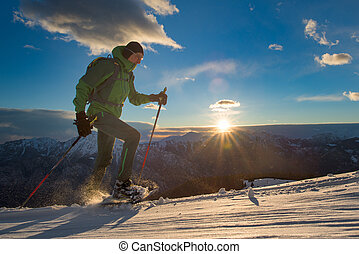 Man practice snowshoeing in a suggestive sunset in the...